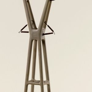 """A model of a high-voltage transmission tower. It is made on a circular base with tall four legged tower with two long arms on the top in the shape of a """"Y""""."""