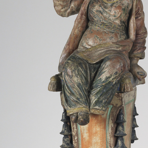A resting figure fanning itself sitting upon a tall column. The figure has pulled back dark hair and is wearing a robe.