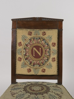 """Chair consists of mahogany frame with thick headpiece that culminates at a central point.  Tapered front and back legs. Front legs terminate in ball feet.  Seat frame curves outwards.  Upholstery on chair back and seat characterized by a buttoned frame.  """"N""""-like medallion in needlepoint embroidered into upholstery."""