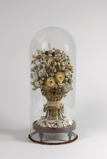Shellflowers assembled in tall bouquet and set in an ornamental vase with glass dome as a mantel garniture; probably English.