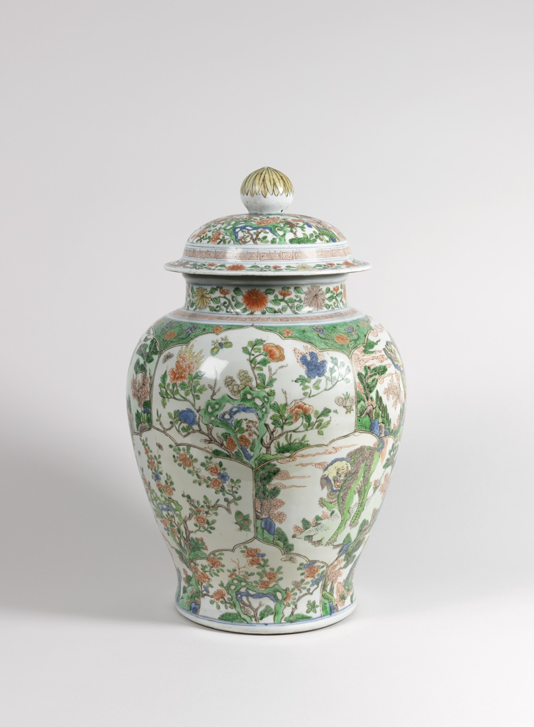Porcelain vase and cover with nature scenes and flowers along the sides and cover.