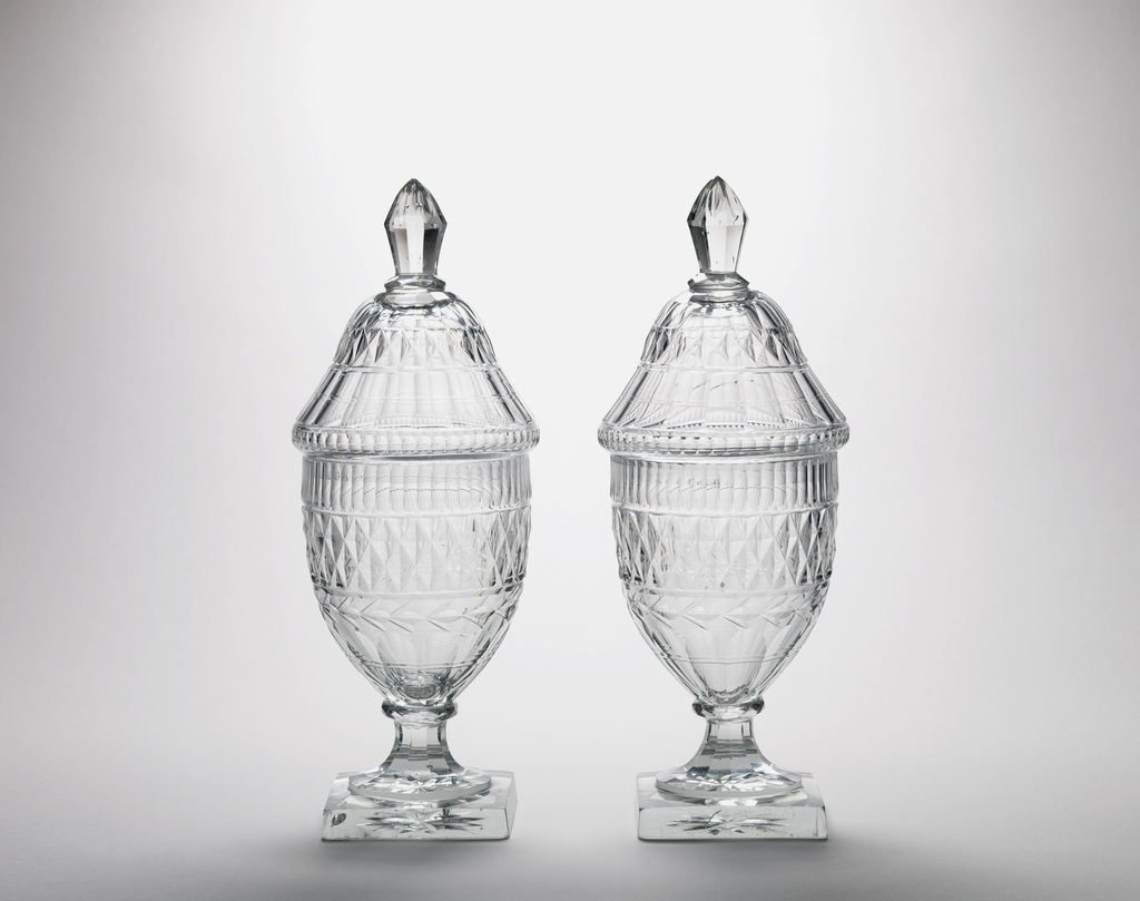 Tall urn-shaped body; tapered, fluted stem; square base with star cutting on bottom; tall domed cover with faceted finial; body cut with row of narrow flutes, band of diamonds, a garland circlet, wide flutes down to base; cover cut with conforming pattern; glass greenish and bubly, heavy.
