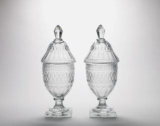 Tall urn-shaped body; short fluted stem; square base with star cutting on bottom; high domed lid with tall faceted finial; body cut with row of narrow flutes, band of diamonds, a garland circlet, wide flutes down to base; cover cut with conforming pattern; glass greenish, bubbly, heavy.