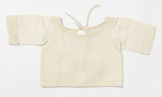 Infant's blouse with tie back closure, scoop neckline, and long sleeves trimmed with lace. Bodice and sleeves of two different off-white cotton fabrics, each with a small diaper pattern.