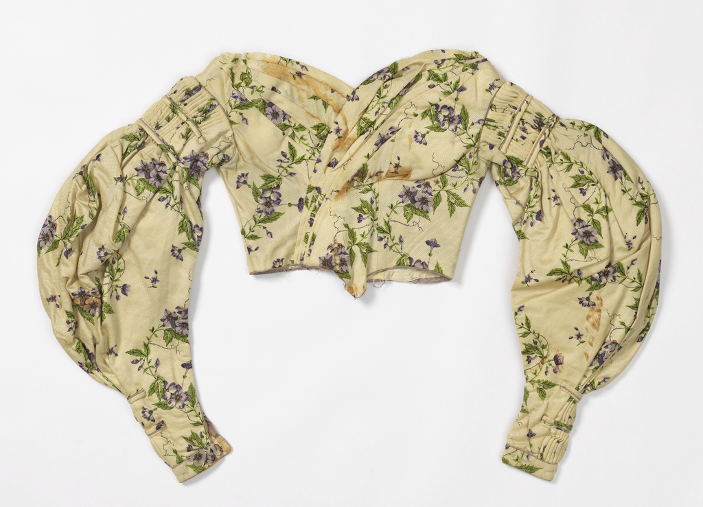 """Fragment composed of bodice of dress: on white, diagonally-striped, waffed ground [silkl warp, wool weft], block-printed pattern in lavender, green and orange, of vertically serpentining flowering vine.  Height of repeat about  9"""".  Goods probably machine-woven.  Skirt has been dismantled.  Bodice: low boned, cross-over folds in front with point, fastens by hook and eye in back; full gigot sleeves tight with shaped, edged with lavender piping as are seams of bodice.  Card packed with dress reads, """"Catharine Beck V.C. 1818-1895"""""""