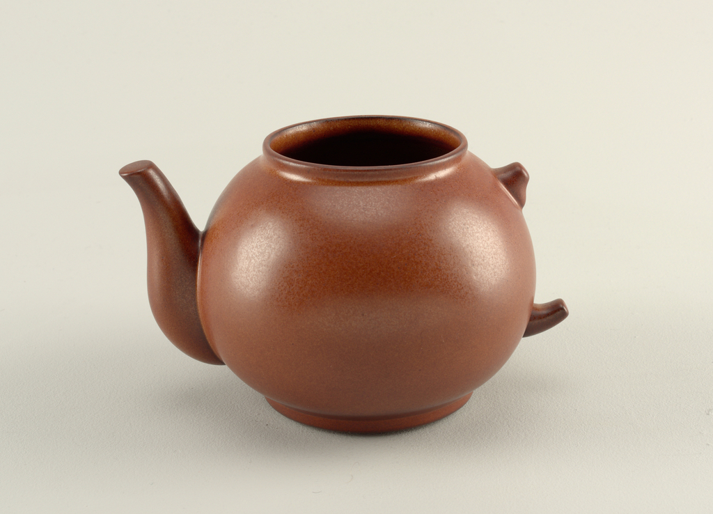 """Matte brown glazed body in form of a globular teapot with wide circular mouth and curved """"spout"""" with sealed end; on opposite side, where loop handle would be, are two short projections suggesting top and bottom of handle."""