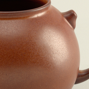 "Matte brown glazed body in form of a globular teapot with wide circular mouth and curved ""spout"" with sealed end; on opposite side, where loop handle would be, are two short projections suggesting top and bottom of handle."