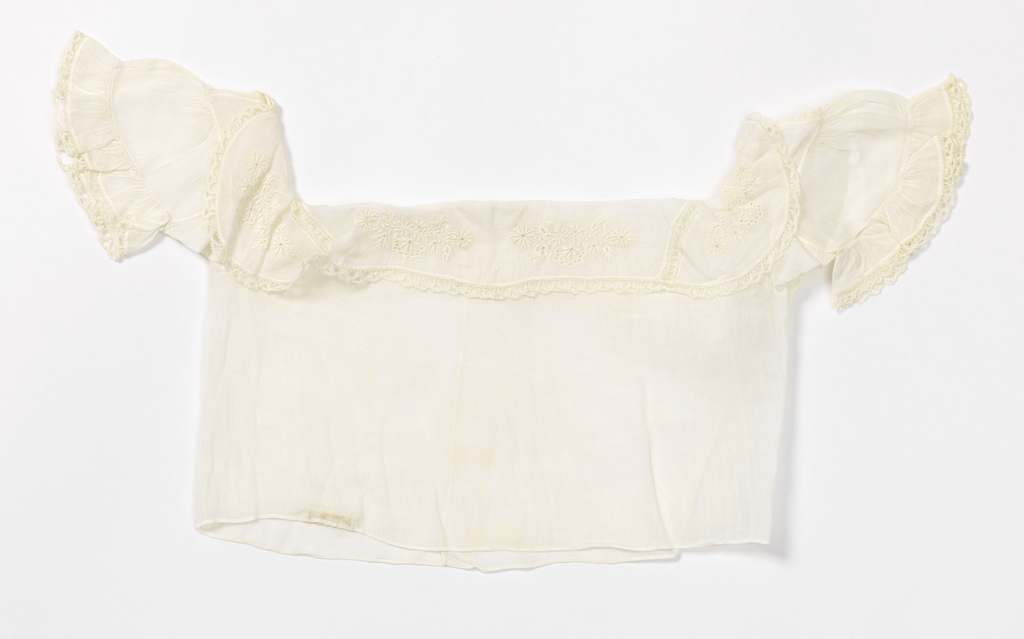 Girl's blouse with back closure, square neckline, and short puffed sleeve with ruffled edge. In off-white cotton batiste with whitework embroidery and lace trimming.