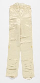 Pair of off-white satin trousers with a drop buttoned front and stirups.