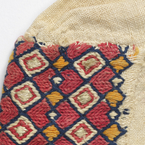 Small cap of white linen embroidered in a diamond pattern in blue, yellow and red.
