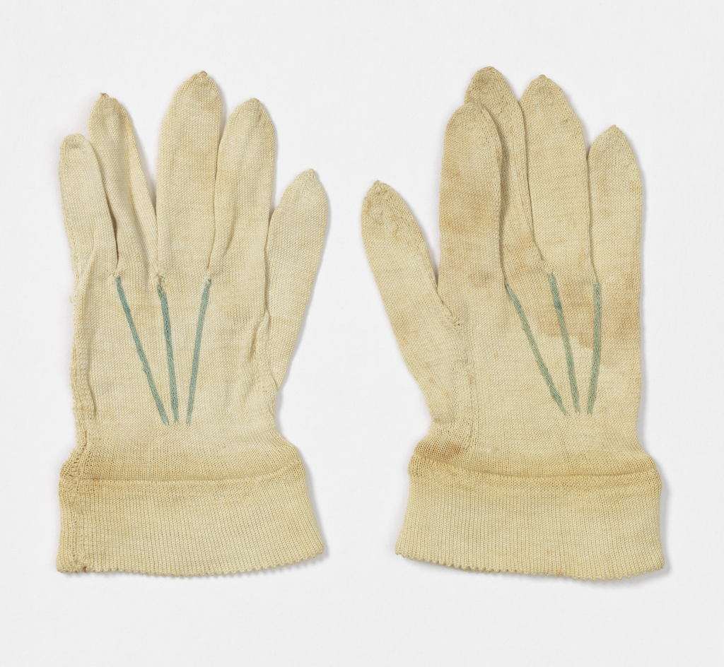 Pair of white silk knitted gloves for an infant, with green stitching on the back of the hand.