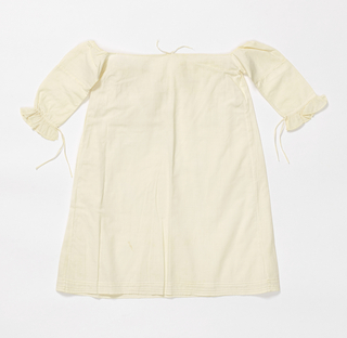 White cotton infant's dress with drawstring neckline, long sleeves with ruffles at the wrists, and tucks around the hem edge.