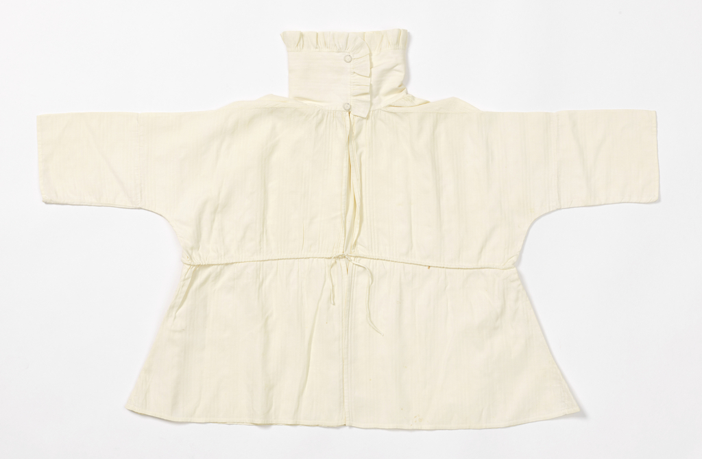 Boy's shirt with a ruffled standing collar, long sleeves, and a drawstring waist. In off-white cotton with vertical ribs.