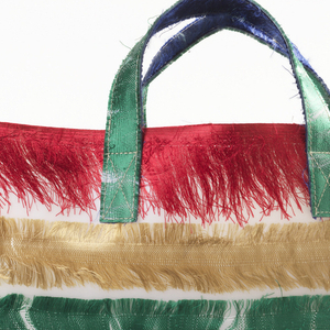Tote bag with stripes of multicolored silk selvedges embedded in polyurethane.