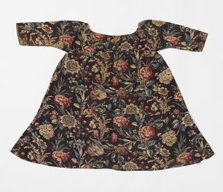 Child's dress with drawstrings around neck and chest, made up of pieces of printed cotton with dark brown groun and large-scale flowers and leaves, in red and blue, with traces of yellow.