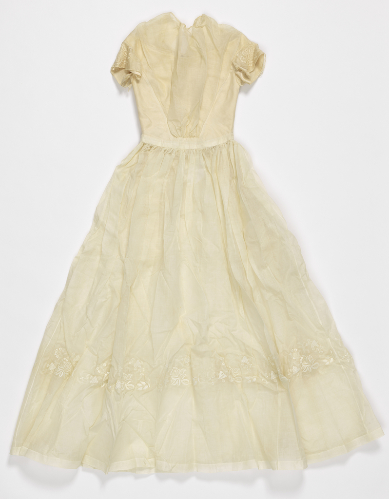 Dress of white cotton batiste with jewel neckline, short sleeves, and long full skirt ornamented with whitework embroidery. Lined bodice, hook and eye closure at center back.