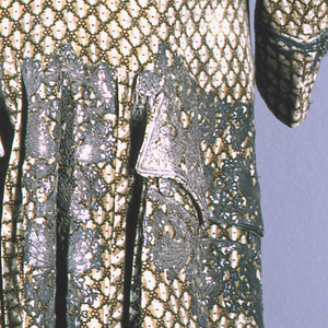 Man's coat of light brown and white vertically striped velvet with small lattice design in green and pink; embroidered with silver, sequins and foil strips. Flowering vines and curving sprays with stars decorate the center front, pockets and pleats in the back.
