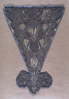 Stomacher with a trefoil point at the bottom, solidly embroidered in silver metallic yarns with a symmetrical design of flowers and leaves, framed by two spiralling ribbons.