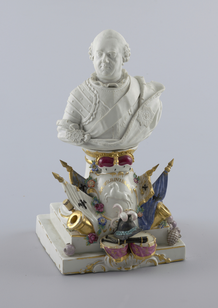 Bisque bust of Herzog August Wilhelm von Braunschwig-Bevern. On the plinth, a crowned shield with a horse, surrounded by flags and military trophies.