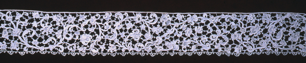 Border of serpentine floral sprays outlined by cordonnet. Pattern connected by brides picotées, outlined by cordonnet and interspersed by portes and gaze quadrillée.