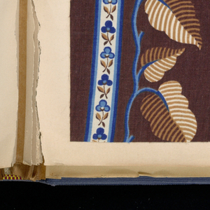 Blue cloth bound volume of 338 samples of printed cotton. Title page has three labels pasted on it. Each pattern is numbered. Most designs form stripes, either floral or geometrical or combinations of both.