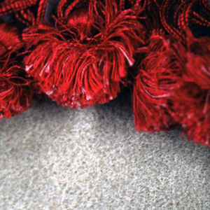 Red woven heading finished with loops and tassels.