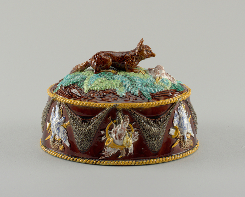 Oval, flat-based dish (a). Sides tapered toward lip, molded with swagged nets alternating with game trophies. At edge of base and lip molded ochre-glazed twisted-rope border. Ground glazed brown, with molded motifs picked out in yellow, white, blue, and brown. Interior glazed with bright mauve; underside mottled green and brown. Oval cover (b) glazed mauve on underside. Exterior molded with central finial in form of a fox on fern fronds and a dead duck. Cover in polychrome colors as on base.
