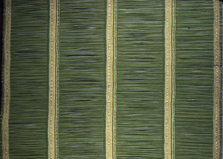 Window blind with rigid wefts and widely spaced warps in shades of green with gold. The wefts are bright green reeds.