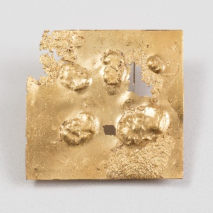 Roughly square form resembling molten, bubbled, gold; cast with five cameo-like female heads in profile, in various sizes, scattered on surface.