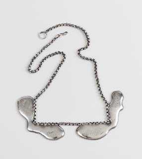 Necklace comprising small-link chain with two rigid poured metal segments creating square corners at bottom.