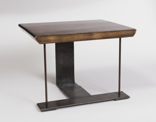 The rectangular wood table top is supported by strap-like iron legs, assembled to form a T-pattern on the ground.