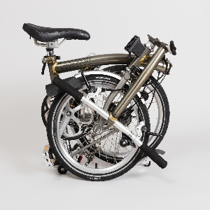 Folding bicycle with a curved frame consisting of a hinged main tube, pivoting rear triangle, fork, and hinged handlebar system. Optional accessory: brown waxed cotton role-top bag attaches to mount at handlebars.