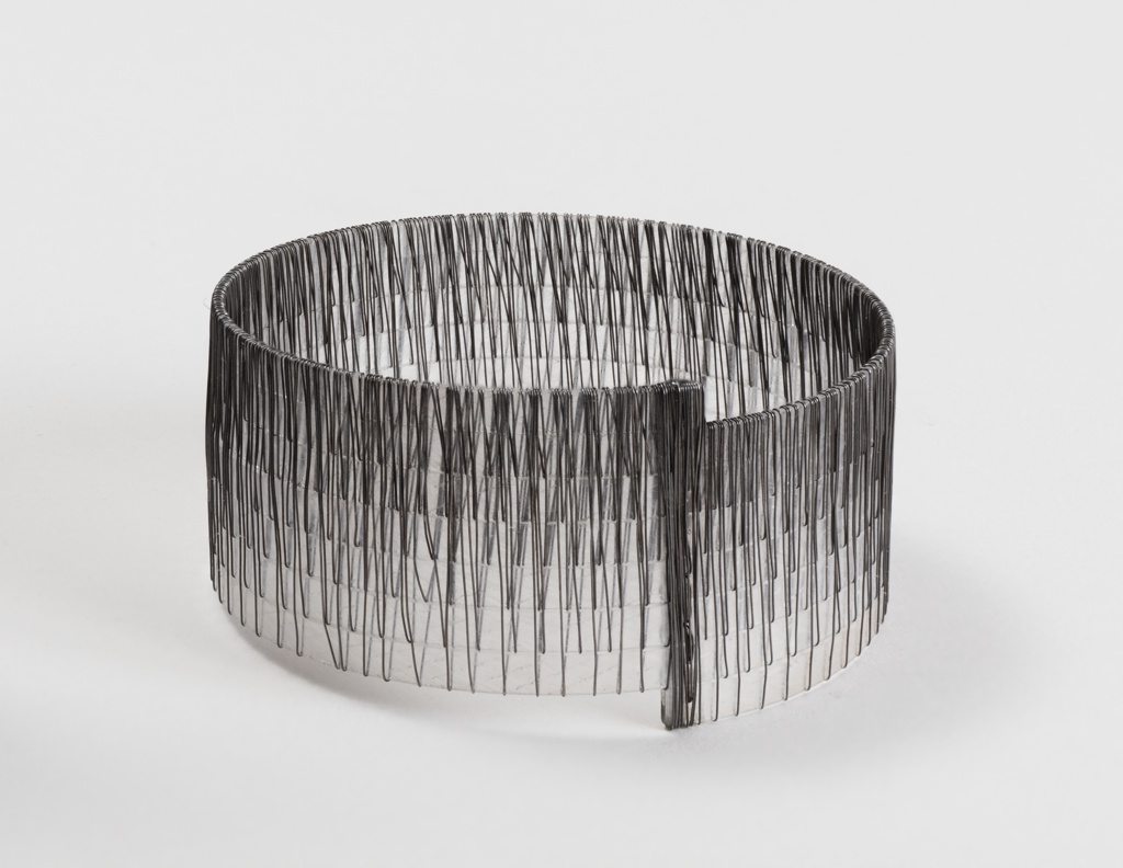 Seven translucent narrow plastic bands wound with a continuous 10-meter length of fine, dark iron wire to form a circular cuff.