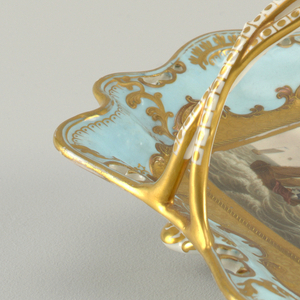 Pair of shallow, pale blue dishes, roughly rectangular with wavy, pierced edges and twisted, c-shaped handle in center; each dish resting on six feet.  A different, detailed marine painting surrounded by heavy gilding on each dish.