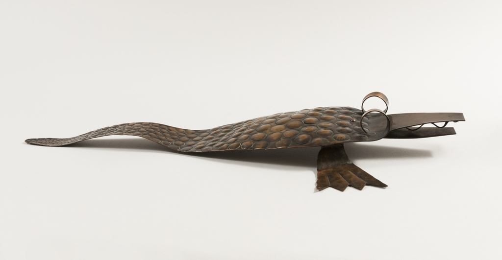 Lizard sculpture studded with convex circles on body with two webbed feet, curls for eyes, and an open mouth with a wavy tongue. Cut from a single sheet of copper except for the feet