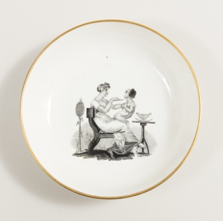 the circular dish with gold rim and a transfer-printed scene in the center of a woman seated on a Greek style chair feeding a child.