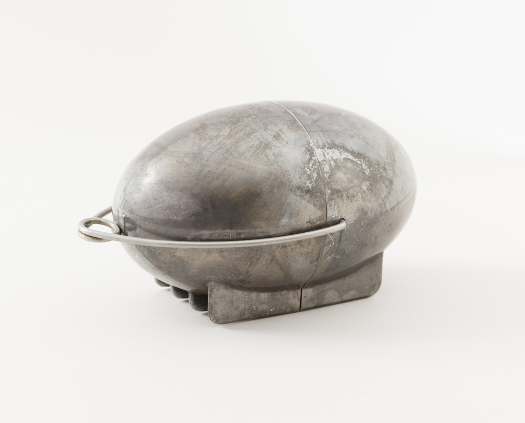 Egg-shaped aluminum shell composed of two halves divided along a central vertical axis; four-glide base for resting on heat source; pivoting wire loop closure/handle attached on sides; interior of larger section with long horizontal skewer to secure potato in device.