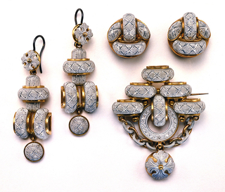 Brooch (a) and earrings (b,c) of aluminum set in elaborate gold mounts and covered with fine bright-cut engraving; brooch with six semi-circular segments surmounting circular form decorated with chevrons, above a linked chain and a small, circular, foliate motif pendant; pendant earrings, each with one horizontal and two vertical semi-circular segments surmounting small, circular, foliate motif pendant.