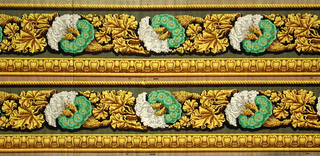 Two identical bands composed of gold molding and gold rope, blossoming wheat stalks surrounded by green floral wreaths alternating with leaves.