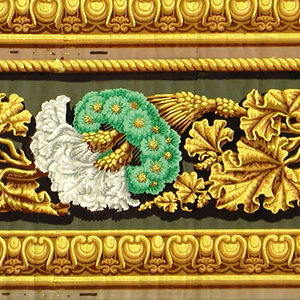 Two identical bands composed of gold molding and gold rope, blossoming wheat stalks surrounded by green floral wreaths alternating with leaves. H# 374