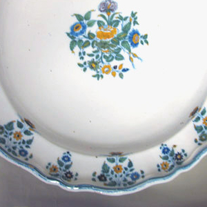 "Shaped rim with blue bands, fleur de pomme de terre (""potato flower""), and central bouquet medallion."