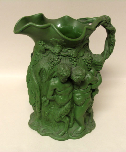 """The dark green version of this pattern was issued in 1831 as model number 19.  While many companies produced versions of the """"Silenus"""" jug, the dark green color is unique to Minton."""