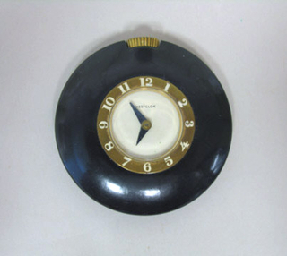 Circular form; smooth black case surrounding brass(?) band with white numerals encircling white face with black hands; brass(?) stem at top.
