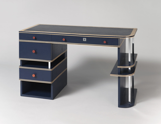 Blue rectilinear form composed of rectangular drawer and shelf unit on left, two-shelf unit on right, supporting two horizontal drawers immediately below desk top; drawer and shelf units with chromed metal supports, square in section; drawers with red conical knobs; desk top covered in blue-painted canvas.