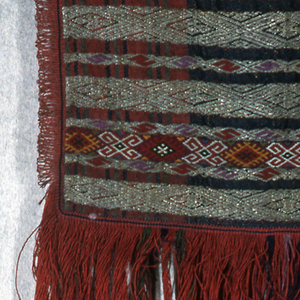 Flat panel of coarse stiff wool, woven in a plaid design of red, blue and green. Horizontal bands embroidered in silver (now tarnished) with additional areas in colored wools. Stylized geometric patterns. Trimmed with narrow red fringe on sides and very deep fringe of red and green at the bottom.