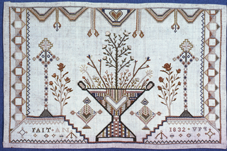 Vase of flowers in center of other ornaments. Sampler may have been made in France or in a school in another country where French was taught to young women.