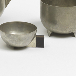 Semi-spherical bowl with metal cuff affixed to a rectangular wooden handle. Stabilizing feet at bottom. Triangular spout. Flat lid with rectangular wooden handle. Slightly tarnished surface.