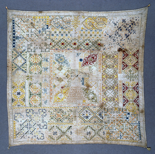 """Central square with decoration and inscription (""""Made by Teresa Alvares in this year 1700"""").  Surrounded by a wide border with corner designs.  Tassels at each corner."""