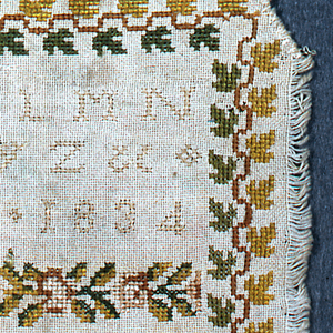 Alphabets, numerals, date and cross border of roses/leaves. Six samples of designs in counted satin surrounded by a leaf border.