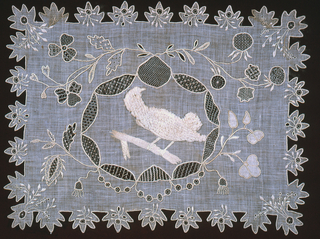 """A bird in """"plush work"""" surrounded by a wreath and flowering branches; the border is cut in tabs, each ornamented with a flower motif."""